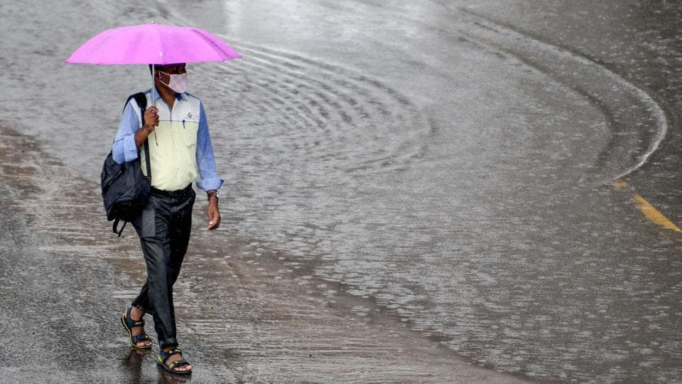 A man carrying an umbrella walks on the roadside under heavy rains in Chennai on November 12. Health minister Harsh Vardhan had said on November 13 that India has initiated an integrated response to overcome the unprecedented Covid-19 pandemic. (Arun Sankar / AFP)