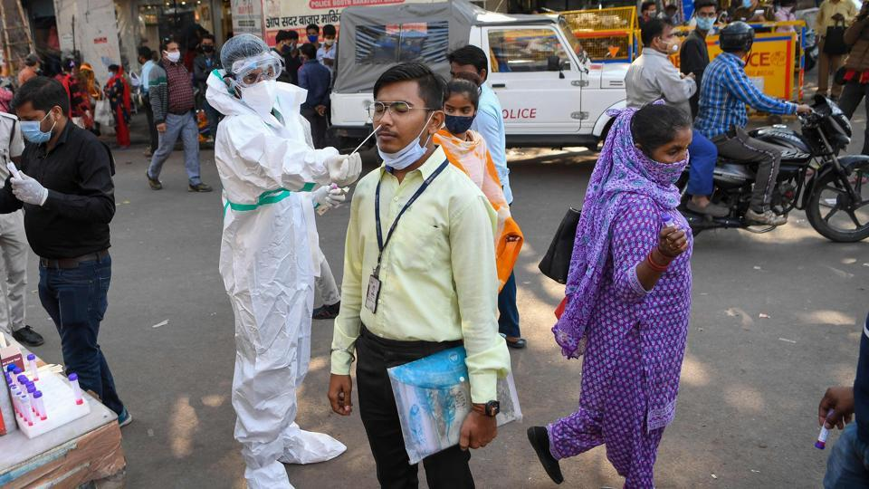 A medical worker collects a swab sample from a man to test for coronavirus infection in New Delhi on November 17. According to Union health ministry, India on November 17 reported 29,163 new cases of the coronavirus disease (Covid-19), the lowest in four months.  (Prakash Singh / AFP)