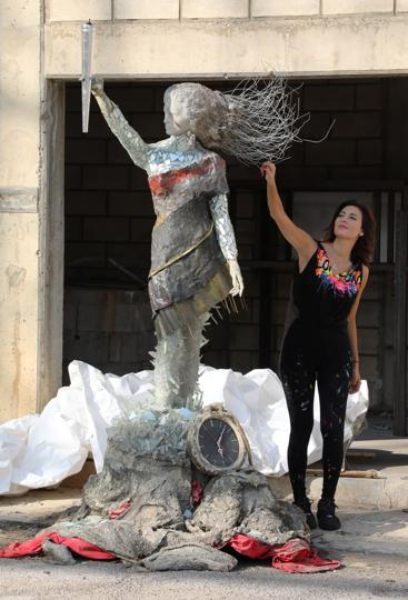 Lebanese artist, Hayat Nazer, poses near her statue made entirely out of broken glass and debris of the August 4 port explosion, during an interview with Reuters in Beirut, Lebanon November 10, 2020. Picture taken November 10, 2020. REUTERS/Mohamed Azakir (REUTERS)