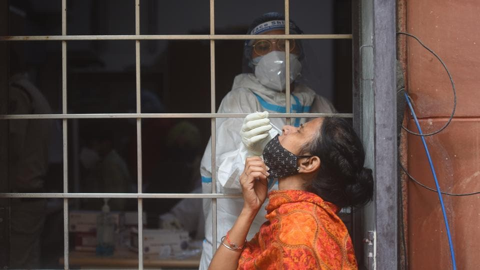 A health worker collects a swab sample for coronavirus testing, at Amar Colony in New Delhi.