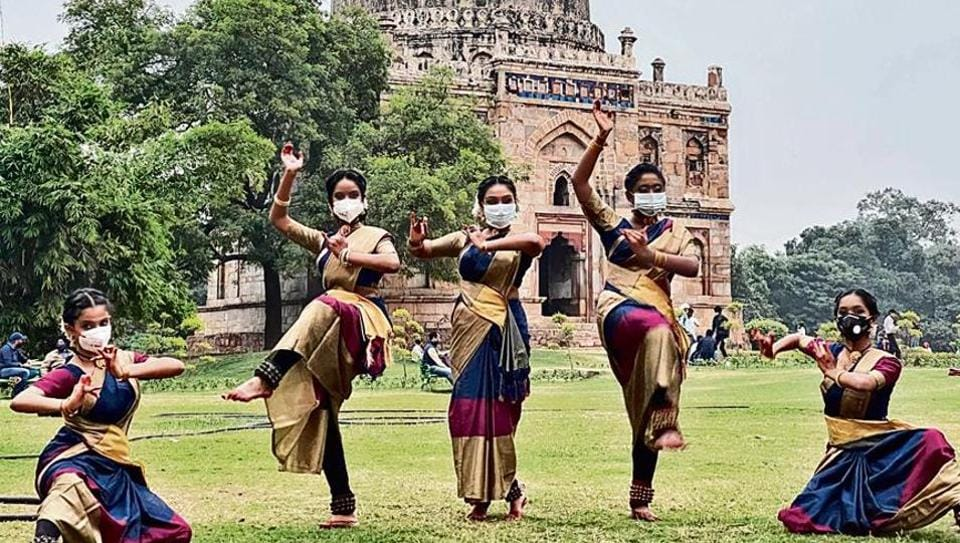 This is a group of young women, wearing the same kind of saris, same kind of bangles, but not the same kind of face masks.