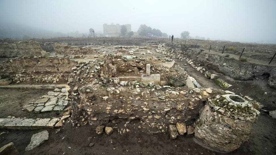 FILE - In this file photo taken on Wednesday, Nov. 18, 2020, a journalist looks at a ruined Tigranakert, Armenian city dating back to the Hellenistic period, in the separatist region of Nagorno-Karabakh.