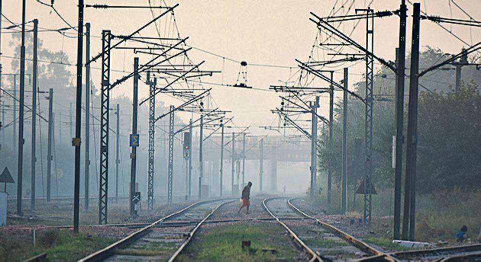 A man crosses a railway track amid hazy weather conditions, at Nizamuddin in New Delhi on November 20.