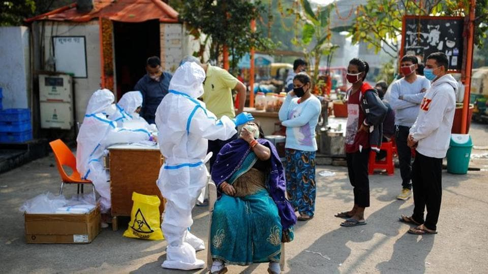 A healthcare worker wearing personal protective equipment (PPE) collects a swab sample of a woman at the Delhi-Uttar Pradesh border in Noida amidst the spread of the coronavirus disease.
