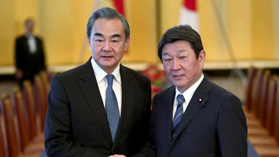 Chinese Foreign Minister Wang Yi, left, poses with his Japanese counterpart Toshimitsu Motegi for a photo prior to a meeting in Tokyo.