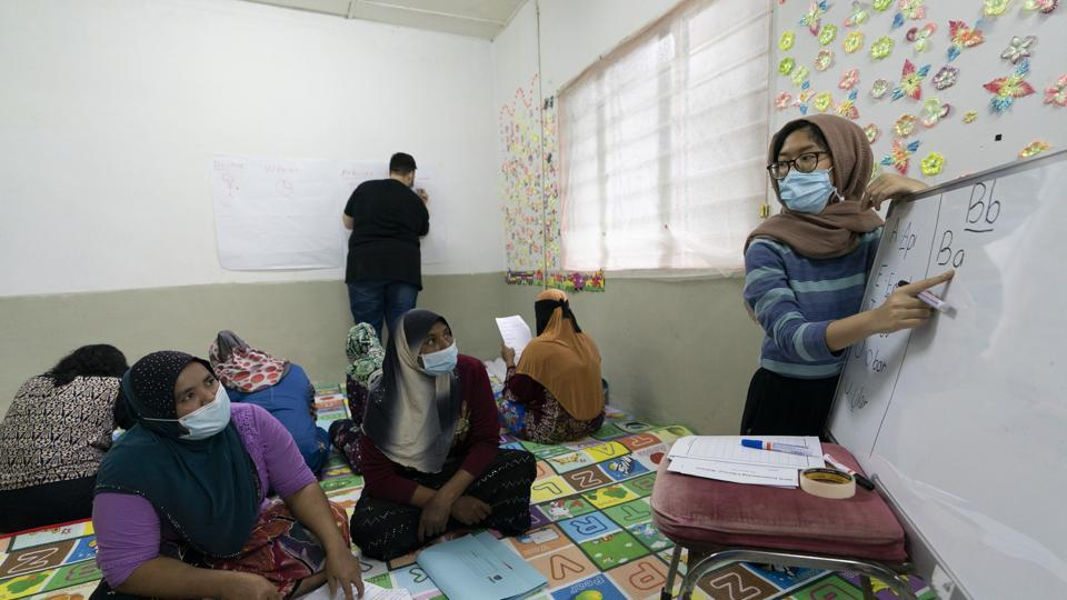 A volunteer teacher, right, gives a basic English lesson to a minority Muslim Rohingya refugees at a slum on the outskirts of Kuala Lumpur, Malaysia.