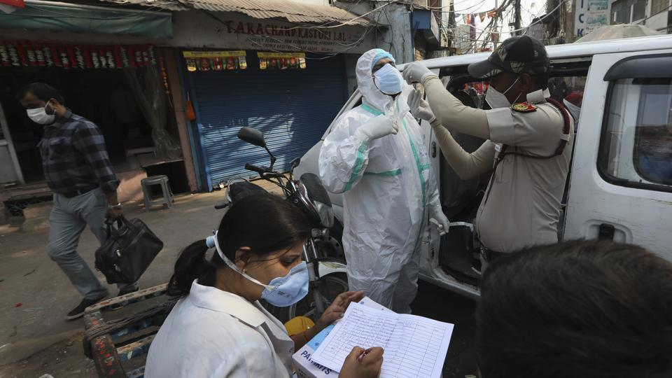 A health worker sitting on a hand cart registers people to test for Covid-19 tests at a market place in New Delhi.