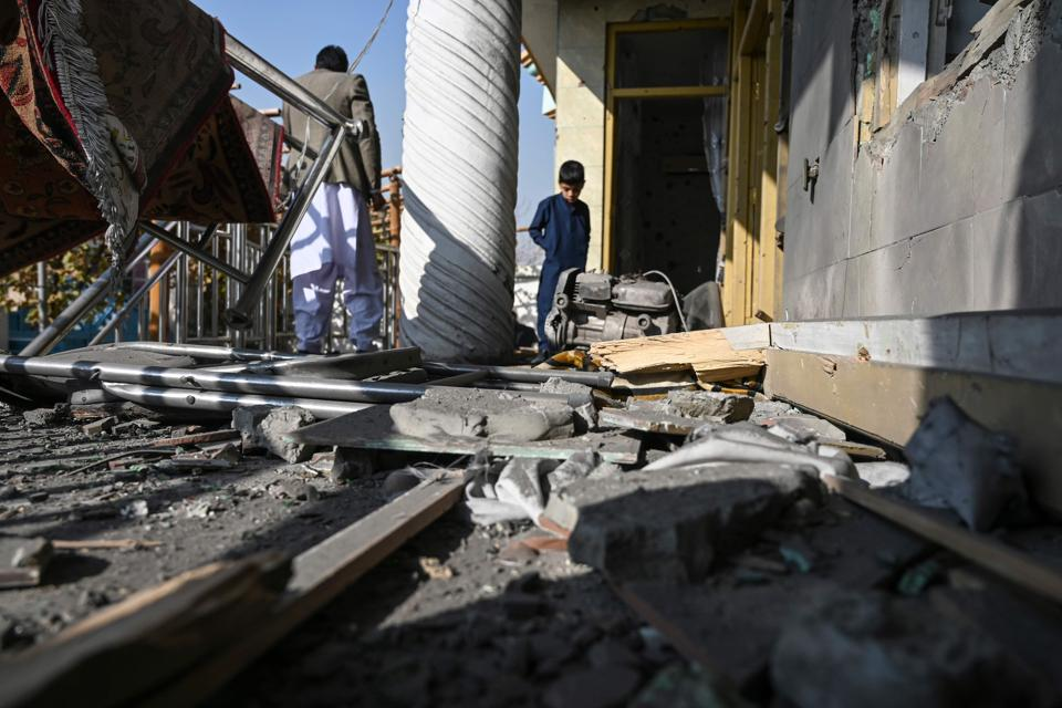 People inspect a damaged house after several rockets land at Khair Khana, north west of Kabul