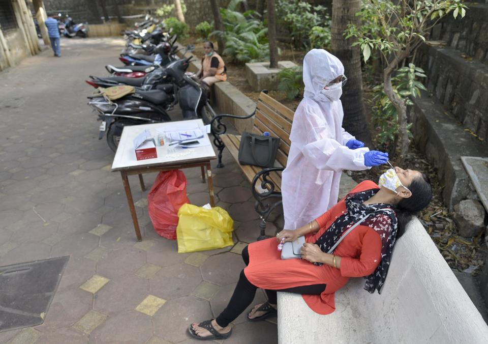 A health worker takes a swab sample of a resident in Malad on Saturday.