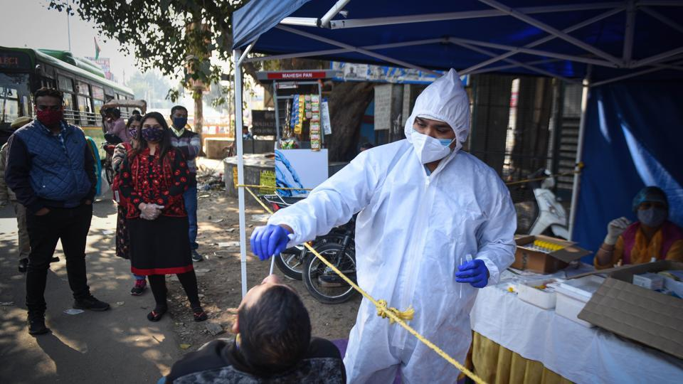 A health worker collects a swab sample to test for coronavirus infection, at Najafgarh, in New Delhi, India, on Friday, November 20, 2020. (Photo by Sanchit Khanna/ Hindustan Times)