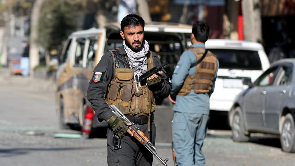 A police officer stands guard after rockets hit residential areas in Kabul, Afghanistan.