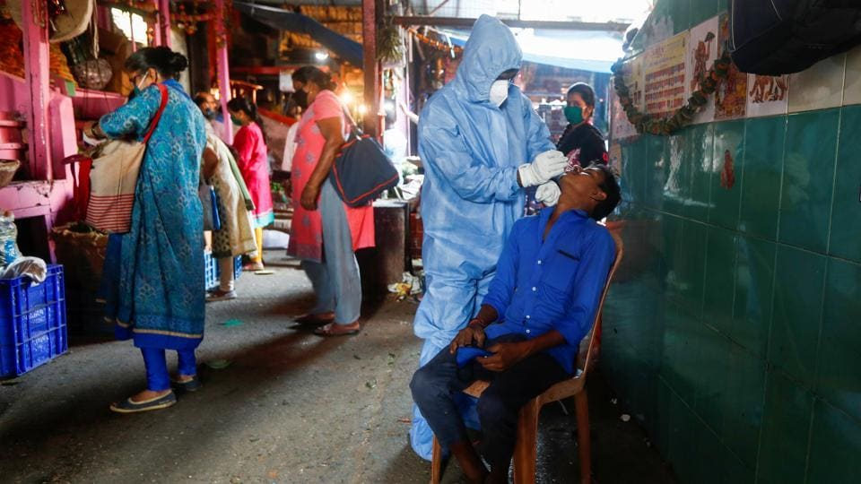A health worker in personal protective equipment (PPE) collects a swab sample from a man during a rapid antigen testing campaign for the coronavirus disease at a vegetable market in Mumbai.