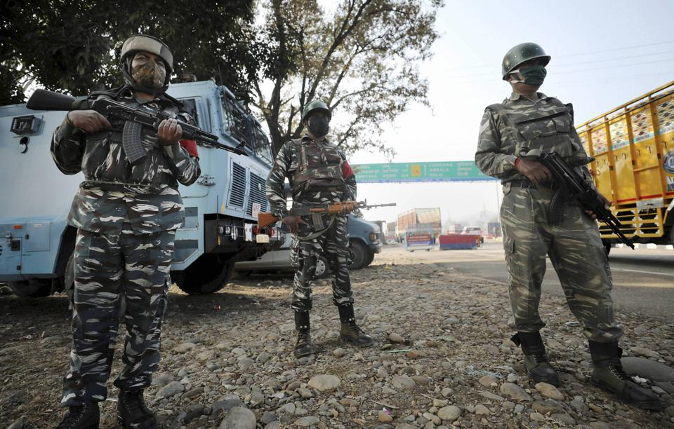 Central Reserve Police Force  (CRPF) personnel stand guard at the Jammu & Kashmir National Highway after  an encounter at Ban toll plaza in Nagrota in Jammu district on November 20.