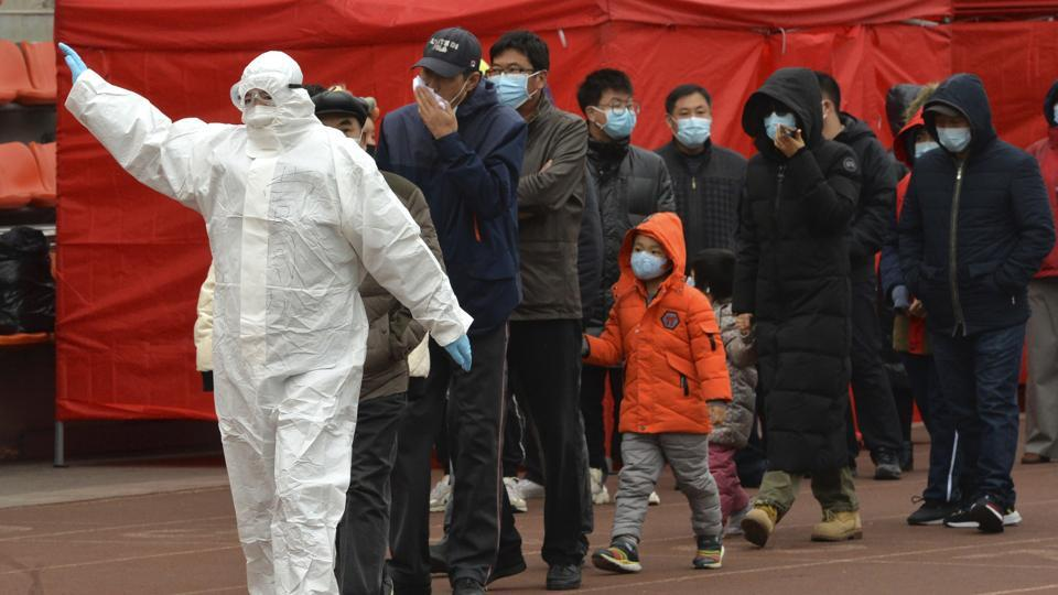 A worker wearing a protective suit gestures to a line of people at a Covid-19 testing site in Tianjin, China,  on Saturday.