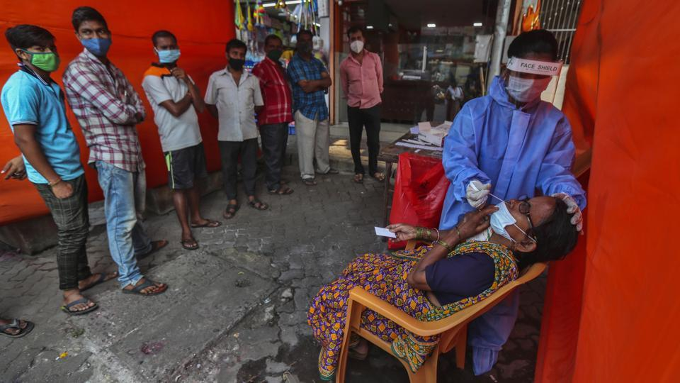 A health worker takes a nasal swab sample from a woman to test for Covid-19 as others wait their turn in Mumbai on November 19. India's tally of confirmed Covid-19 cases, currently the second largest in the world behind the United States, crossed 9 million on November 21 according to data from the Union Health Ministry. (Rafiq Maqbool / AP)