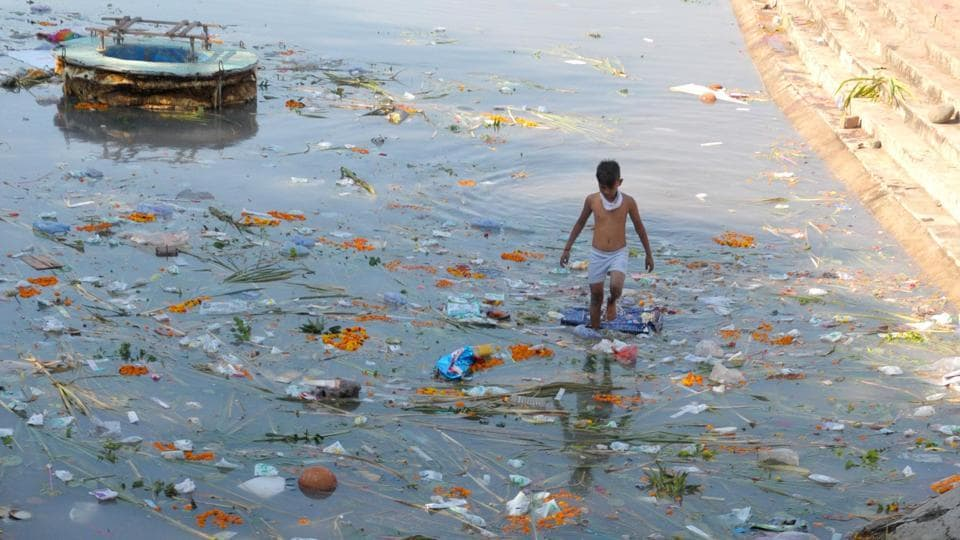 A kid scours for useful items in the remnants left floating behind after the four-day Chhath Puja culminated at the Sector 42 lake in Chandigarh on Saturday.