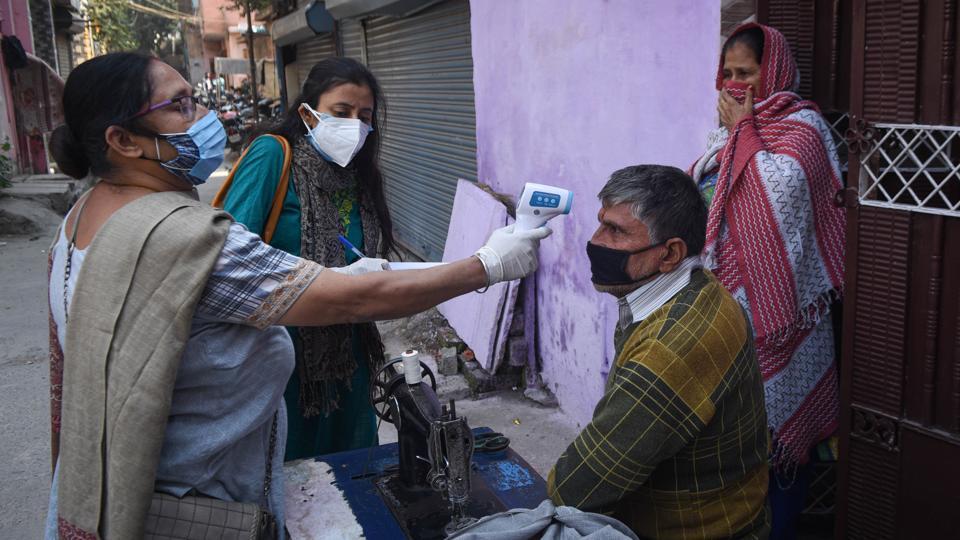 District administration personnel thermal screening people during door to door Covid-19 surveys at Raghubir Nagar in New Delhi.