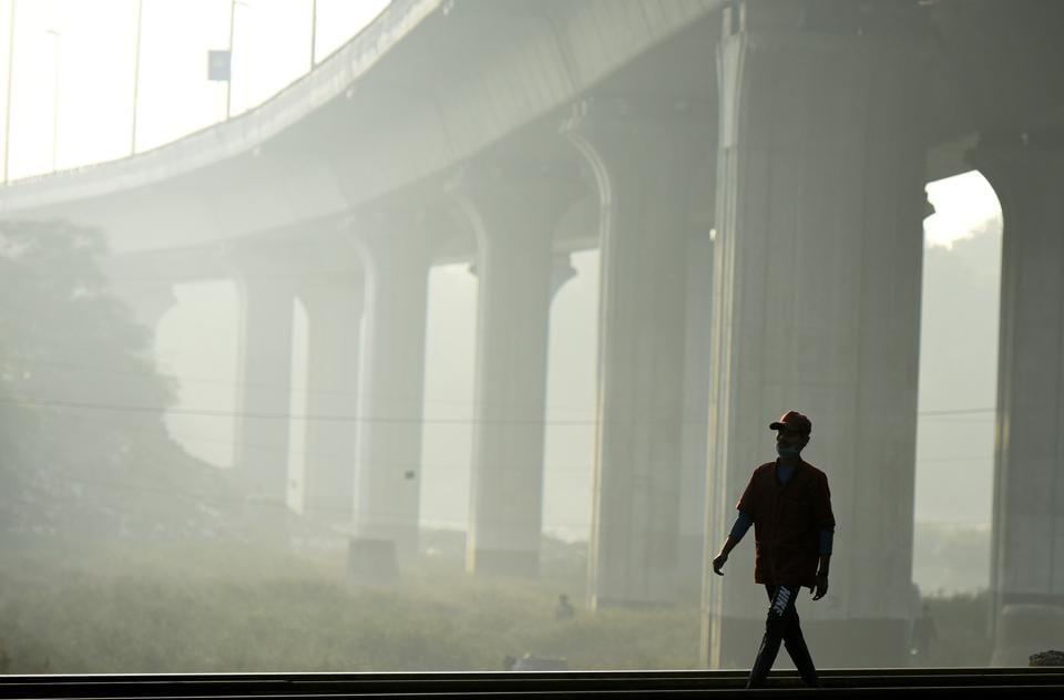 A boy walks along a railway track amid hazy weather conditions at Nizamuddin in New Delhi on November 20.