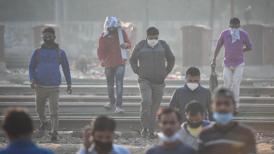 People  walk across railway tracks on a cold morning, in Patel Nagar, New Delhi.