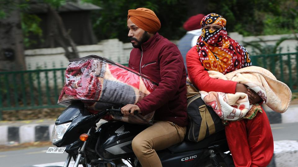 Commuters ride along Mall Road with winter warmers in Patiala on November 20. According to scientists, winter has arrived in many parts of northwest India, both in the hills and the northern plains, with the minimum temperature dipping 5 degrees Celsius below normal in several cities, HT reported. (Bharat Bhushan / HT Photo)