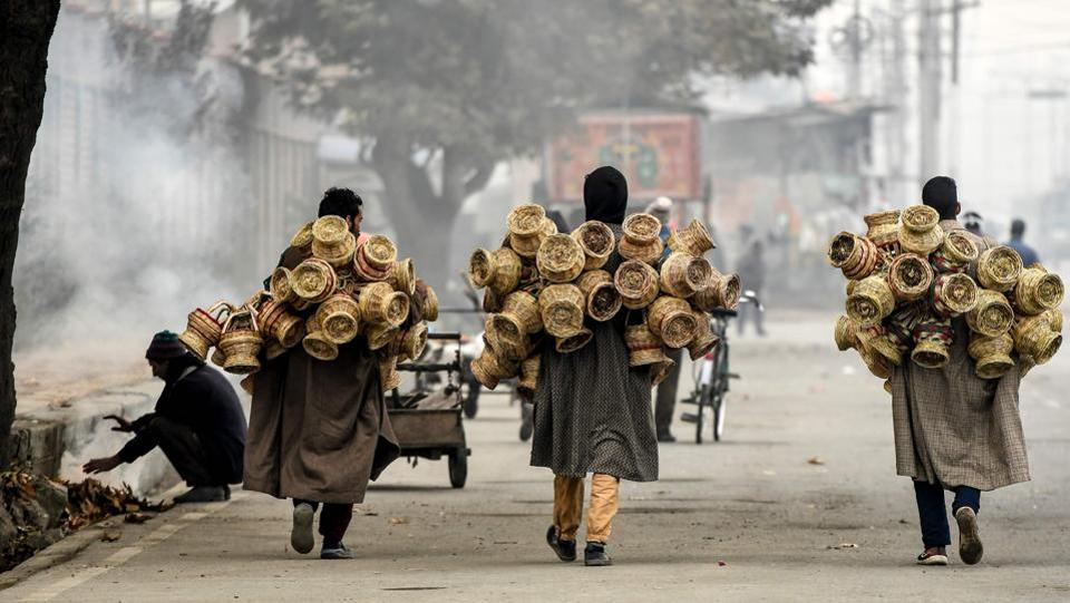 Hawkers carry Kangri (earthen pots covered with wicker) on a cold day in Srinagar on November 19. According to Kuldeep Shrivastava, due to back-to-back western disturbances, the weather department expects snowfall in the hills to continue - which means that minimum temperatures will gradually fall further after the next western disturbance passes. (Tauseef Mustafa / AFP)