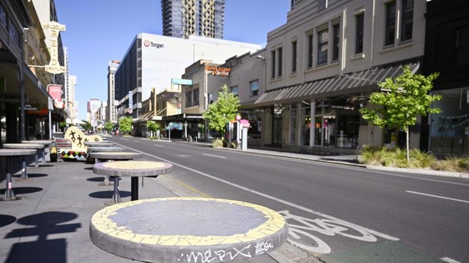 Tables stand vacant in a nearly empty pedestrian mall in Adelaide, Australia.