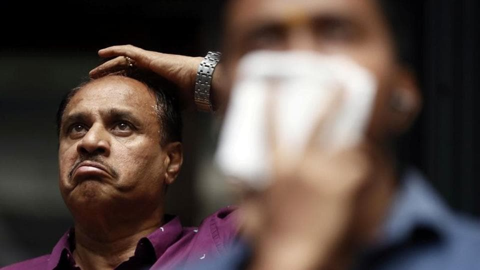 A man reacts as he looks at a screen displaying the Sensex results on the facade of the Bombay Stock Exchange (BSE) building in Mumbai.