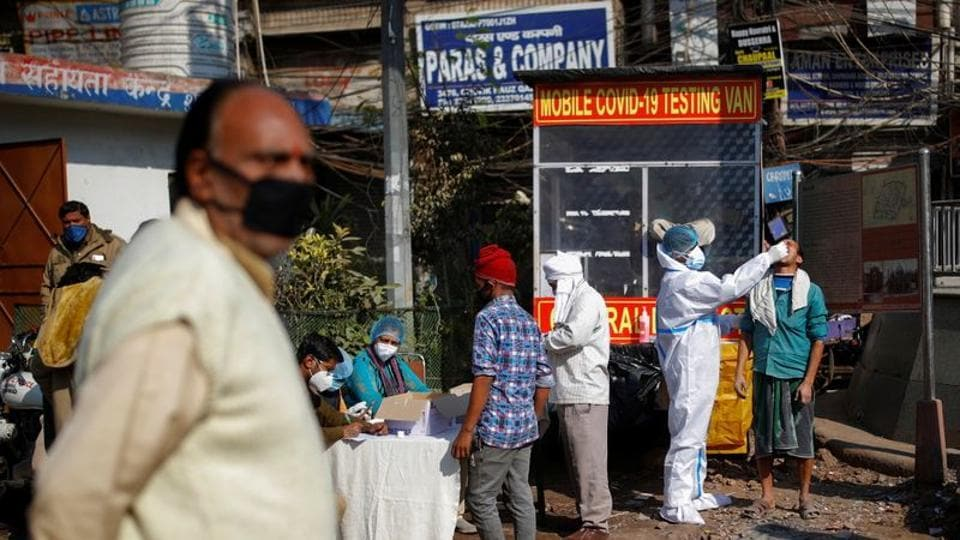 A healthcare worker wearing personal protective equipment (PPE) collects a swab sample from a man, amid the spread of coronavirus disease (COVID-19), in the market area in Old Delhi .