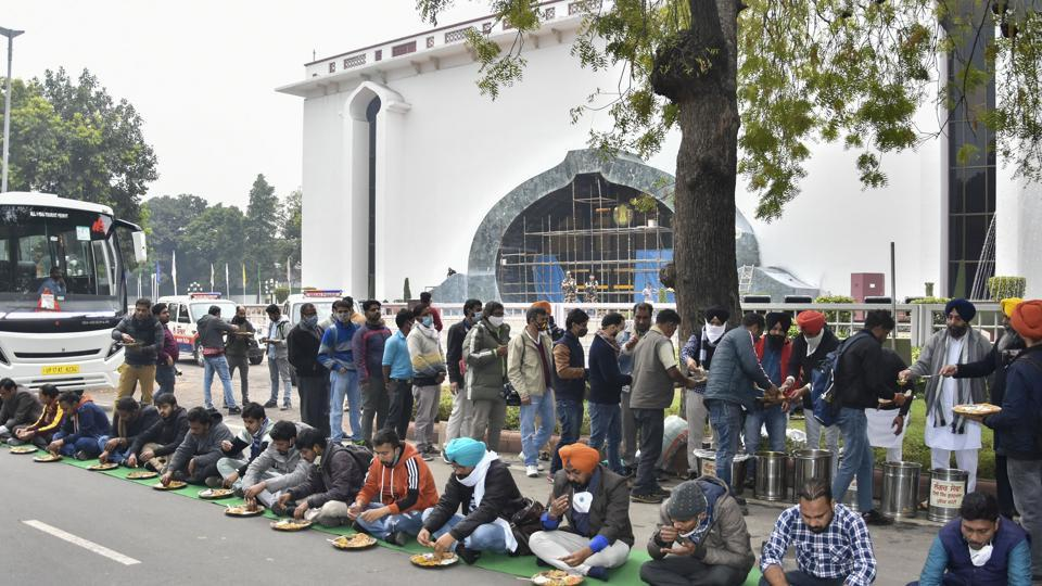Famers and their supporters have 'langar', arranged by Delhi Gurdwara Management Committee, outside the Vigyan Bhavan during their talks with the government over farm reform laws in New Delhi on Monday.