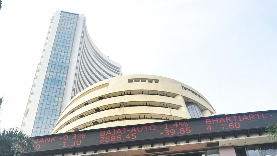 Mumbai: People walk in front of a digital screen at the facade of BSE, as the Sensex crossed 48000 mark for the first time, in Mumbai, Monday, Jan. 4, 2021. (PTI Photo/Shashank Parade)