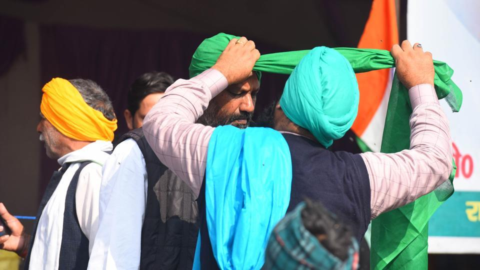 A demonstrator helps another tie a turban during the ongoing sit-in protest against new farm laws, at Ghazipur border in New Delhi, India, on Monday, January 4, 2021. (Photo by Raj K Raj/ Hindustan Times)