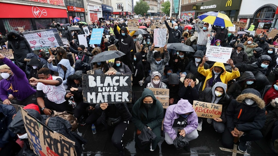 Demonstrators wearing protective face masks and face coverings hold placards during a Black Lives Matter protest in Leicester, following the death of George Floyd who died in police custody in Minneapolis, Leicester, Britain, June 6, 2020.