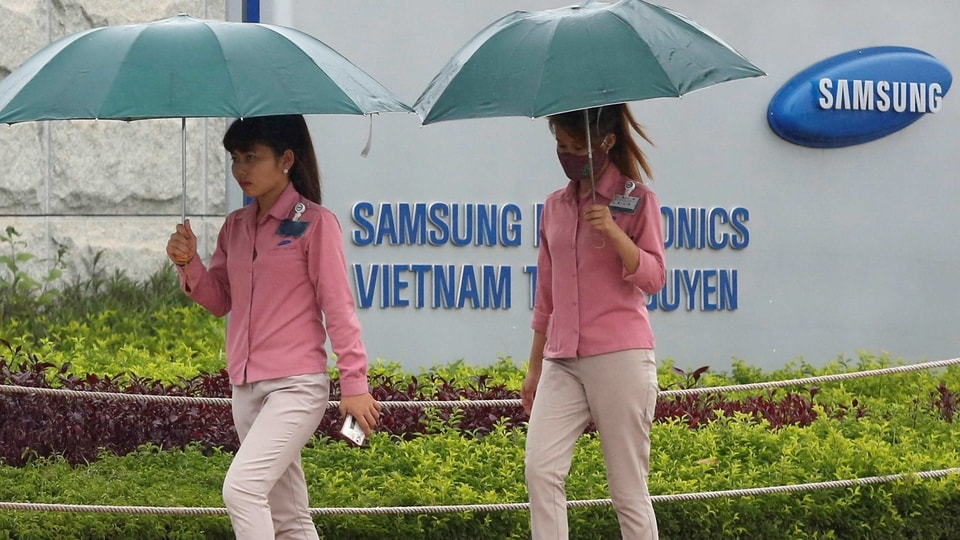 An employee (L) holds a smartphone as she is on the way to work at the Samsung factory in Thai Nguyen province, north of Hanoi, Vietnam.
