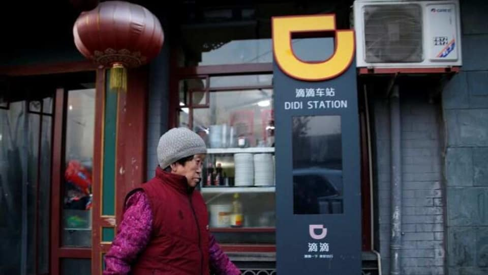 A woman walks past a sign of station for Didi Chuxing in Beijing, China.