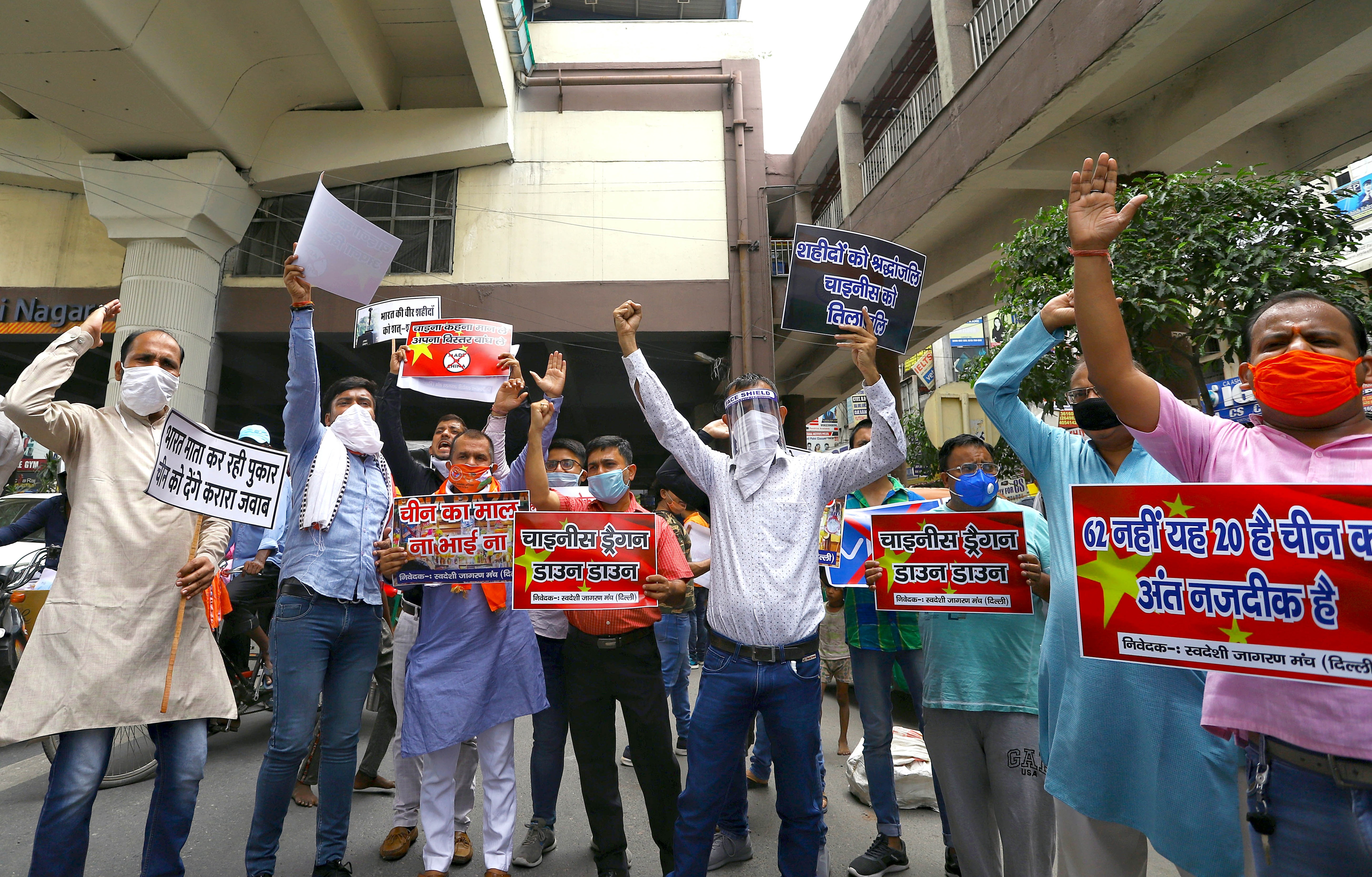 Swadeshi Jagran Manch workers hold a placard and shout slogans as they protest against Chinese goods and against the killing of Indian soldiers during India China clash, at Laxmi Nagar in New Delhi on Saturday.