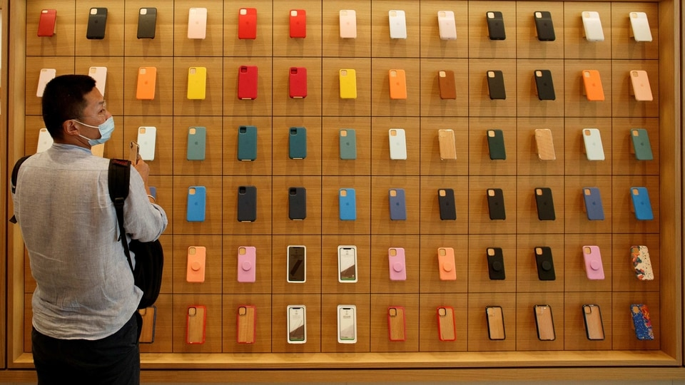 A man stands in front of a wall of iPhones cases in the new Apple flagship store on its opening day following an outbreak of the coronavirus disease (Covid-19) in Sanlitun in Beijing, China.