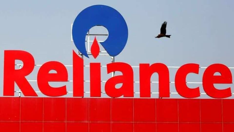 A bird flies past a Reliance Industries sign in Ahmedabad, India.