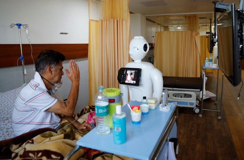 A patient suffering from the coronavirus disease (Covid-19) speaks to his family members, using a robot named 'Mitra' at the Intensive Care Unit (ICU) of the Yatharth Super Speciality Hospital in Noida