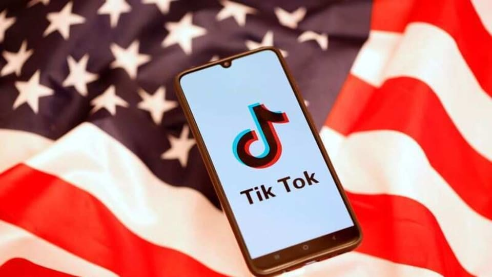 TikTok logo is displayed on the smartphone while standing on the US flag. REUTERS/Dado Ruvic/Files