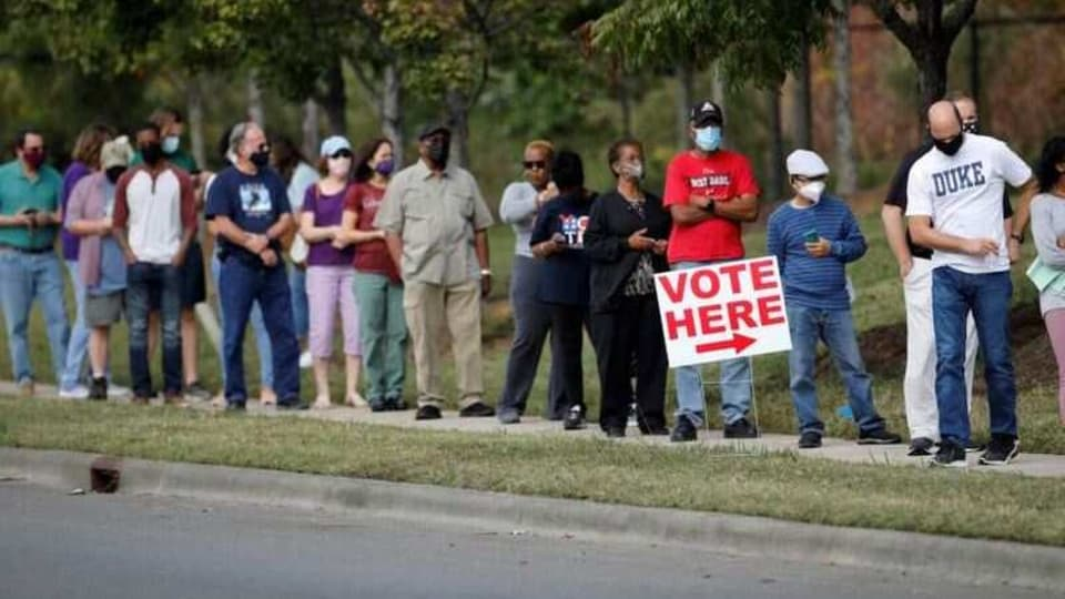 Voters wait in line to enter a polling place and cast their ballots on the first day of the state's in-person early voting for the general elections in Durham, North Carolina, US October 15, 2020.
