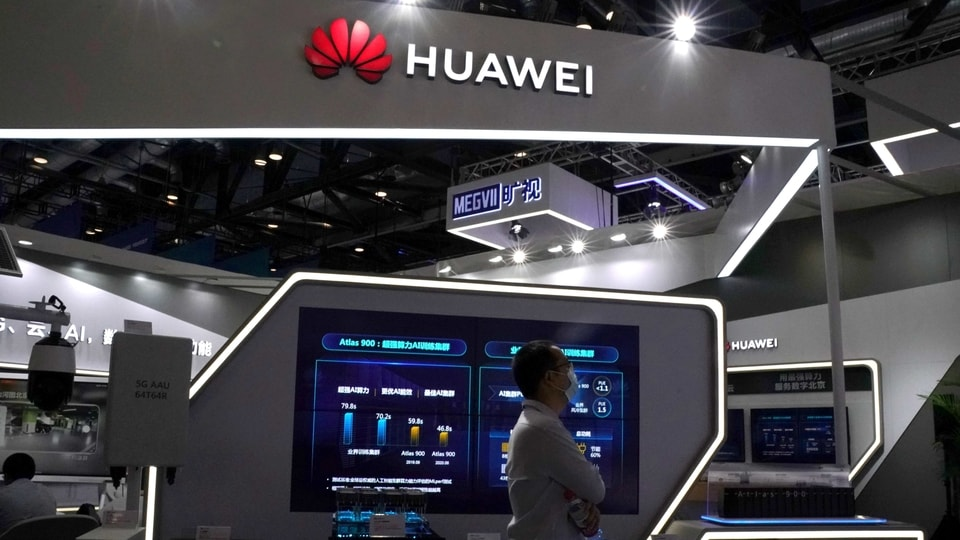 FILE PHOTO: A man wearing a face mask following the coronavirus disease (COVID-19) outbreak walks past a booth of Huawei at the 2020 China International Fair for Trade in Services (CIFTIS) in Beijing, China September 4, 2020. REUTERS/Tingshu Wang/File Photo