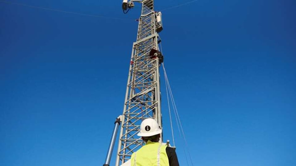 A worker stands in front of a mobile tower in Denver, U.S., August 31, 2020. Picture taken August 31, 2020. DISH NETWORK/Handout via REUTERS THIS IMAGE HAS BEEN SUPPLIED BY A THIRD PARTY. NO RESALES. NO ARCHIVES MANDATORY CREDIT.