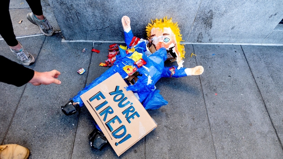 A pinata representing President Donald Trump rests on the ground as several hundred people celebrate the victory of President-elect Joe Biden and Vice President-elect Kamala Harris in San Francisco.