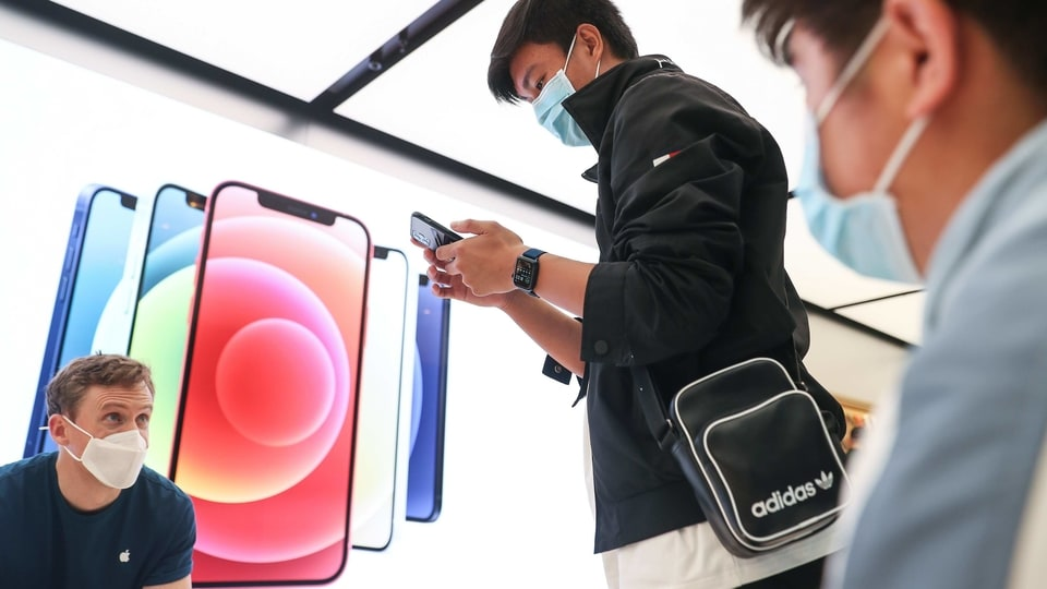 A customer wearing a protective mask tries out an Apple Inc. iPhone 12 Pro Max at the Apple flagship store during a product launch event in Sydney, Australia.