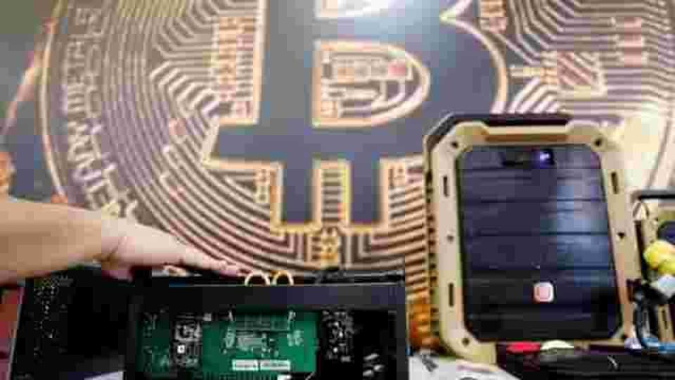 FILE PHOTO: A cryptocurrency mining computer is seen in front of bitcoin logo during the annual Computex computer exhibition in Taipei, Taiwan