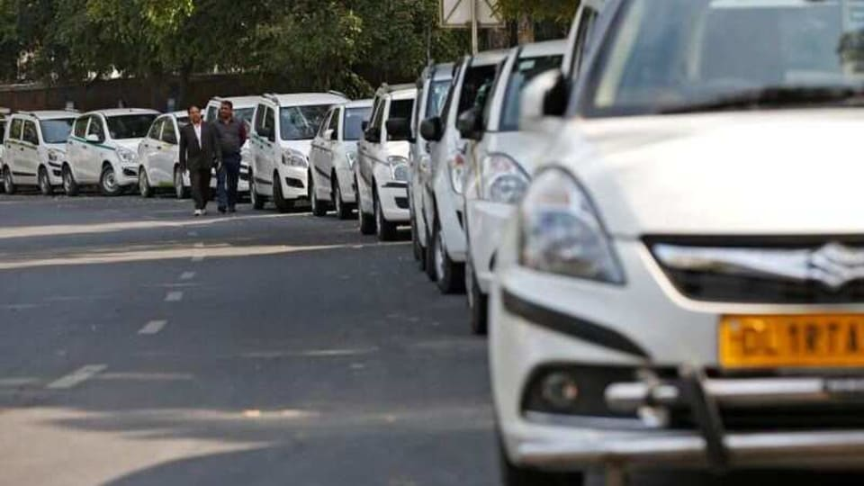 Drivers of Uber and Ola walk next to their parked vehicle's during a protest in New Delhi, India, February 14, 2017. REUTERS/Adnan Abidi/File Photo