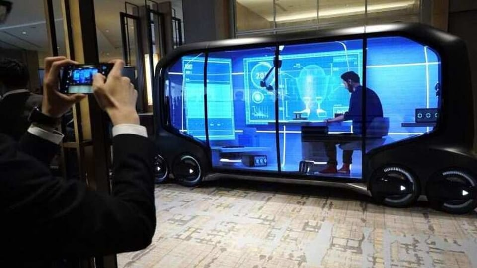 Toyota's e-Palette is a largely transparent, driverless oblong carriage on wheels that's powered by a battery. It can accommodate up to 20 passengers, with seats that fold up and allow the space to be re-purposed.
