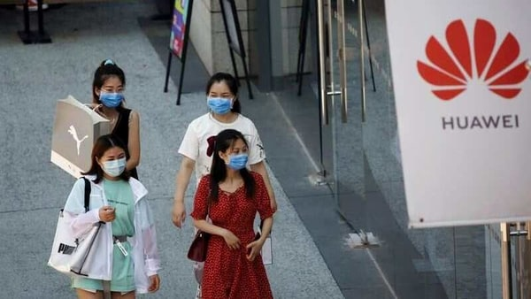 FILE PHOTO: Women wearing face masks following the coronavirus disease (COVID-19) outbreak walk past a Huawei store at a shopping complex in Beijing, China, July 14, 2020. REUTERS/Tingshu Wang