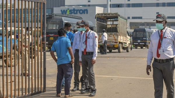 Security personnel stand guard outside Wistron Infocomm Manufacturing India Pvt Ltd, where a section of workers went on a rampage at its facility manufacturing Apple iPhones and other products over non-payment of promised wage, at Narasapura area in Bengaluru.