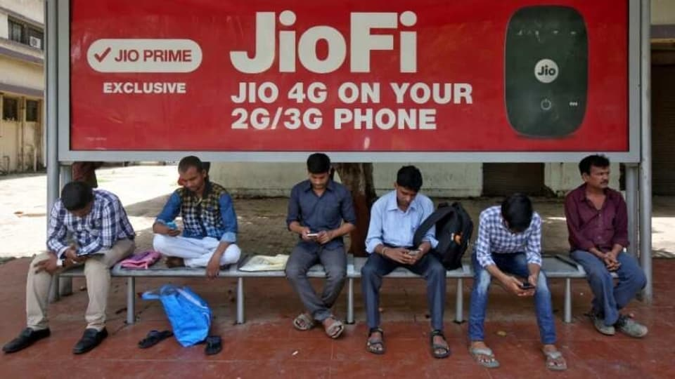 Commuters use their mobile phones as they wait at a bus stop in Mumbai.